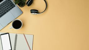 Office workspace yellow desk table with laptop, coffee, mobile, notebook, plant. Flat lay royalty free stock photography