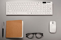 Office workstation with a keyboard, notebook, pen and glasses Stock Photography