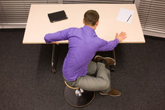 Office yoga - business man exercising at  desk Royalty Free Stock Photos