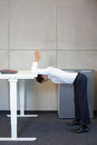 Office yoga - business man exercising at high desk Stock Images