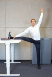 Office yoga - business man exercising at high desk Stock Photo