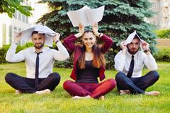 Office yoga. Three young employees in a lotus pose are sitting on green grass and meditate. Recreation of office staff. Healthy li Royalty Free Stock Image
