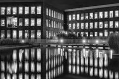 Officebuilding i Zoetermeer, Nederländerna vid natt med reflexion i vattnet i svartvitt royaltyfria foton