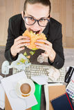 OfficeCoffee break. Junk food office worker Lunch. Sandwich at the work table. hunger . Top view Royalty Free Stock Images