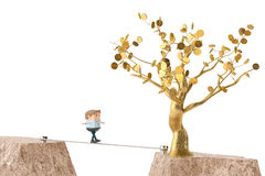 An officeman walking on steel rope over canyon, go to gold tree. Royalty Free Stock Photo