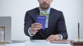 Officer holding passport with euros, payment for id card services, migration. Stock footage stock footage