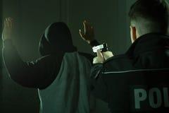 Officer keeping gun on crook Stock Photos