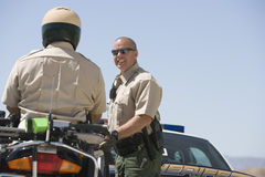 Officer Looking At Coworker Sitting On Motorbike Royalty Free Stock Photography