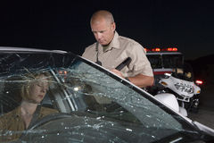 Officer Looking At Unconscious Woman In Car Stock Photos
