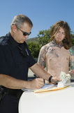Officer Making A Drug Bust. Male police officer writing ticket for arrested drug dealer Stock Photos