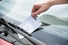 Officer's hand putting parking ticket on car royalty free stock images