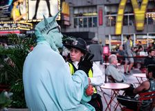 NYPD Police officer seen talking to a street entertainer in Times Square, New York City, USA. The officer is seen giving words of advice to a street entertainer Stock Photo