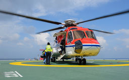 The officer take care passenger to embark helicopter at oil rig. Platform royalty free stock image