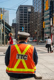 Officer of  Toronto Transit Commission. Observing traffic in downtown, at University Avenue and King Street West. TTC is public transport agency that operates Stock Photo
