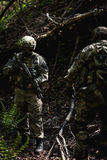 Officer with weapons on reconnaissance. Military officer with weapons on reconnaissance in forest among trees stock photography