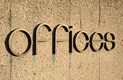 Offices Sign. Offices in large bronze letters on a concrete wall Stock Image