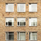 Offices with wall windows. Wall of a residential block of flats with balconies windows Stock Photos