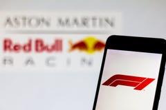 Officiële F1 FIA Formula 1 embleem op het mobiele apparatenscherm Embleem van het Aston Martin Red Bull Racing team op de achterg stock fotografie