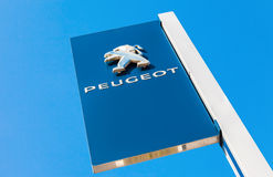 Official dealership sign of Peugeot against the blue sky backgro Royalty Free Stock Photos