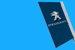 Official dealership sign of Peugeot against the blue sky backgro Stock Photo
