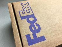 Official FedEx brown shipping package box. Official worldwide FedEx brown package shipping box. FedEx Corporation is an American global courier delivery services Stock Photo