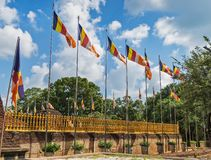 Official flags of the Buddhism flutter on wind. A lot of official flags of the Buddhism flutter on wind in a sunny weather, standing вряд along a fence of Royalty Free Stock Image