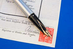 Official form : stamp duty. A macro image of an official form for registering births and deaths showing the Registrar's signature handwritten over a postage Royalty Free Stock Photography
