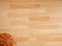 An official orange ball on a basketball court. An official orange ball on a hardwood basketball court Royalty Free Stock Image