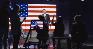 Official conducting press conference on stage. Official press conference of American representative politician on stage against display with American flag giving Royalty Free Stock Image