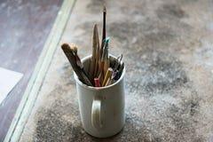 In officina ci sono molti strumenti differenti per gli artigianato in tazze fotografia stock