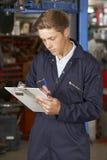 Officina riparazioni di Working In Auto del meccanico dell'apprendista Fotografie Stock Libere da Diritti