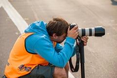 Offizieller Fotograf, der Fotos mit einem DSLR und einem Zoomobjektiv machend sich duckt lizenzfreies stockfoto