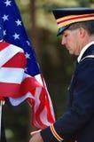 Offizier in der Armee, der die Markierungsfahne anhebt Lizenzfreie Stockbilder