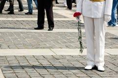 Offizier in der weißen Uniform hält Gartennelkenblumen auf Victory Day in Kyiv, Ukraine Stockfotografie