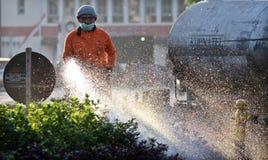Offizier-Surakarta-Gemeindeverwaltungs-Hygieneabteilungen nehmen Sorgfalt des Stadtparks mit einem Schlauch mit Wasser jeden Morg Stockfotografie