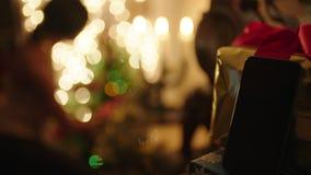Offlinetelefon mit Geschenkbox und aus der Fokusfrau heraus, die Weihnachtsbaum auf dem Hintergrund verziert stock video footage