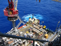Offloading Boat. Offloading cargo from a supply boat onto an offshore oil & gas platform Stock Images