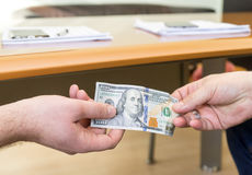 Offre d'homme de cent billets d'un dollar Les mains se ferment vers le haut Concept de corruption Photographie stock libre de droits