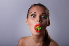Offre de femme de sourire votre cerise mûre de goût Photographie stock libre de droits