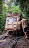 offroad корабль 4x4 вставленный на грязной грязной улице с молодым человеком пробуя взять ее в дождевом лесе Камеруна, Африки стоковые фото
