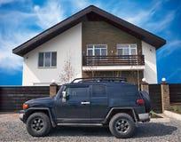 Offroad auto dichtbij het Nieuwe huis van de Luxe Stock Afbeeldingen