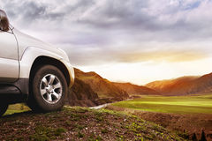 Offroad car concept with mountains. Offroad car concept. Big car wheel on background of mountains and sunset Stock Image