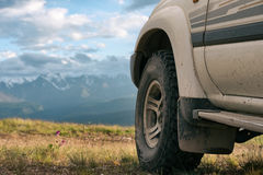 Offroad car concept with mountains. Wheel close-up. Offroad car concept with mountains. Wheel close-up Royalty Free Stock Photos