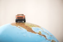 Offroad car on globe. Miniature concept Stock Photography