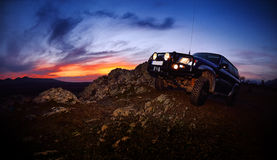 Offroad car on mountain road. At sunset Stock Photo