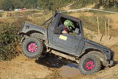 Offroad car is overcoming a difficult terrain Royalty Free Stock Image