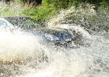 Offroad car splashing water. Silver offroad car driving in a river and splashing water stock image