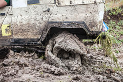 Offroad car stuck in deep mud with flat tyre. Stock Photo