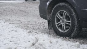 Offroad car with winter tires rides on a snowy road in daytime in snowfall. Wheels closeup in slow motion. Bad weather