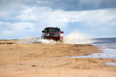Offroad driving. Big four-wheel car driving on sandy sea coast in water splashes Royalty Free Stock Image